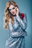 Beautiful elegant girl in brilliant paillettes dress. Portrait of beautiful elegant woman in brilliant fashionable paillettes dress on blue background in studio Royalty Free Stock Photos