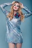 Beautiful elegant girl in brilliant paillettes dress. Portrait of beautiful elegant woman in brilliant fashionable paillettes dress on blue background in studio Royalty Free Stock Image