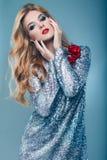 Beautiful elegant girl in brilliant paillettes dress. Portrait of beautiful elegant woman in brilliant fashionable paillettes dress on blue background in studio Stock Photos