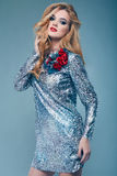 Beautiful elegant girl in brilliant paillettes dress. Portrait of beautiful elegant woman in brilliant fashionable paillettes dress on blue background in studio Royalty Free Stock Photo