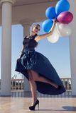 Beautiful elegant girl with dark hair with colorful baloons
