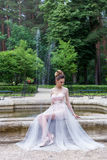 Beautiful elegant girl in evening dress with beautiful evening festive hairdo near fountain Royalty Free Stock Photos