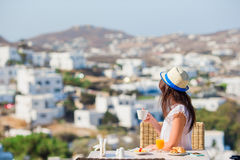 Beautiful elegant girl having breakfast at outdoor cafe with amazing view on Mykonos town. Woman drinking hot coffee on Stock Photos