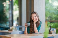 Beautiful girl with hot coffee having breakfast at outdoor cafe. Happy young urban woman drinking coffee Stock Image