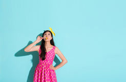 Beautiful elegant girl holding lollypop candy. Touching mouth and looking at above standing in blue background with cute dress clothing Stock Images