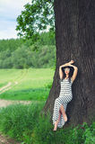 Beautiful elegant girl  leaning against ancient oak in spring Royalty Free Stock Photography