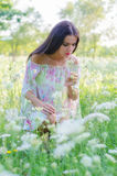 Beautiful elegant girl with long hair smelling elder flowers in spring Stock Photo