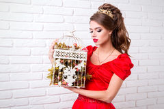 Beautiful elegant girl in a long red dress and shoes holds a bir Royalty Free Stock Photo