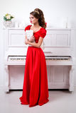 Beautiful elegant girl in a long red dress and shoes holds notes Royalty Free Stock Image