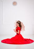 Beautiful elegant girl in a long red dress and shoes sits on the Stock Photography