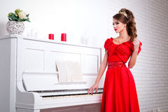 Beautiful elegant girl in a long red dress and shoes is standing Stock Photos