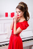 Beautiful elegant girl in a long red dress and shoes is standing Royalty Free Stock Images