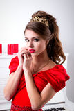 Beautiful elegant girl in a long red dress and shoes is standing Stock Image