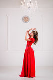 Beautiful elegant girl in a long red dress and shoes is standing Royalty Free Stock Photography
