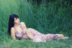 Beautiful elegant girl lying in high grass in summer Stock Images