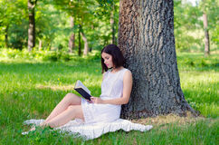Beautiful elegant girl reading book in the forest in summe. Beautiful elegant girl reading book in the forest on sunny summer day Royalty Free Stock Photo