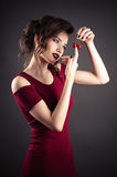 Beautiful elegant girl in red dress with cherry in hands Royalty Free Stock Photos