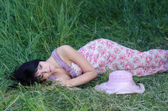 Beautiful elegant girl sleeping in high grass in spring. Beautiful elegant girl sleeping in high grass in summer royalty free stock photos