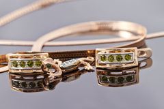 Beautiful and elegant gold earrings with emeralds and a pendant Stock Image