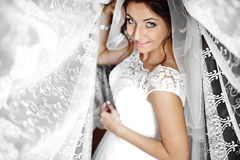Beautiful elegant happy brunette bride on the background of a tu. Lle in a room in the morning Royalty Free Stock Photo