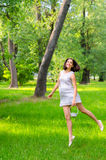 Beautiful elegant happy girl in white dress jumping in spring forest Stock Photos