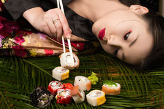 Beautiful elegant Korean girl lying on table and eating rolls. Closeup Stock Photography
