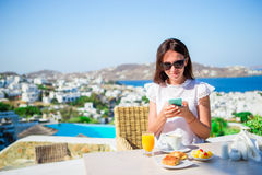 Beautiful elegant lady on breakfast with phone at outdoor cafe with amazing view on Mykonos town. stock image