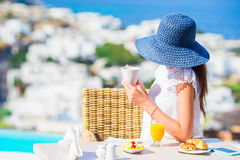 Beautiful elegant lady having breakfast at outdoor cafe with amazing view on Mykonos town. Woman drinking hot coffee on Stock Photo
