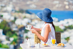 Beautiful elegant lady having breakfast at outdoor cafe with amazing view on Mykonos town. Woman drinking hot coffee on Royalty Free Stock Photos