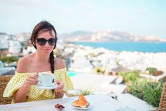 Woman drinking hot coffee on luxury hotel terrace with sea view at resort restaurant. Stock Photo