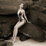 Beautiful elegant lady at huge boulder. Beautiful elegant lady with a huge boulder on the seashore Royalty Free Stock Photos