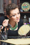 Beautiful elegant lady putting make up at home Royalty Free Stock Images