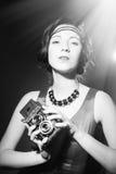 Beautiful elegant lady with retro camera. Black Stock Image
