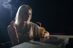 Beautiful elegant lady sitting alone in the night club and smoki Stock Images
