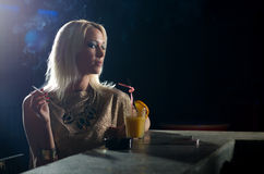 Beautiful elegant lady sitting alone in the night club and smoki Stock Photo