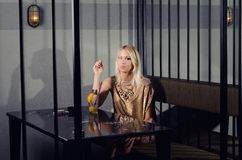 Beautiful elegant lady sitting alone in the night club Royalty Free Stock Photos