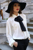 Beautiful elegant ladylike woman in blouse and felt hat stock photography