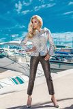 Beautiful elegant luxury sexy stunning blonde model wearing a jacket and trousers stands on a yacht Stock Photos