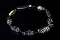 Beautiful, elegant necklace of black agate stone on a black background. Royalty Free Stock Photos