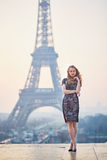 Beautiful elegant Parisian woman near the Eiffel tower. At early morning Royalty Free Stock Images
