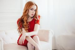 Beautiful elegant redhaired woman in a red dress royalty free stock images
