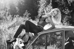 Beautiful, elegant, girl blonde in jeans in black shoes sits on the old car in the forest stock photos