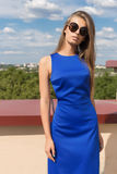 Beautiful elegant trendy stylish young girl with long hair in sunglasses and bright makeup in blue dress posing for the camera on. The terrace Stock Photos
