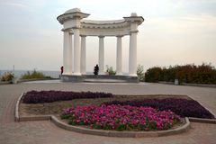 Beautiful and elegant White altanka in Poltava, Ukraine. Beautiful and elegant White arbor in a park with a bright purple flowers in Poltava, Ukraine royalty free stock photography