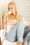 Beautiful elegant woman barefoot drinking coffee Royalty Free Stock Photos