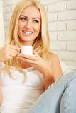 Beautiful elegant woman barefoot drinking coffee Royalty Free Stock Image