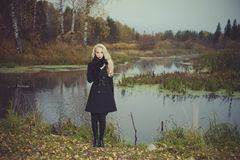 Beautiful elegant woman in a black coat. On the river bank Stock Image