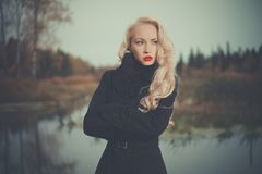 Beautiful elegant woman in a black coat. On the river bank Royalty Free Stock Photo