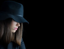 Beautiful elegant woman in black suit and black hat. Holding gun isolated on black background Royalty Free Stock Image