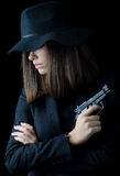 Beautiful elegant woman in black suit and black hat holding gun. Isolated on black background Stock Photo